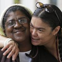 Photo - Sherene Julian, right, hugs her friend Robin Howard outside the Anna Louise Inn, in Cincinnati on Thursday, May 16, 2013. The two are residents of the home for struggling women. In a deal with Western & Southern Insurance Group, who bought the 104-year-old inn for $4 million, the women now living there will remain where they are for two years as a new facility for them is built. (AP Photo/Al Behrman)