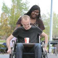 Photo - Volunteer Clea'rissa Bobo helps Joiner Darrell Potter navigate a wheelchair through an obstacle course with a cup of water on a tray as part of disability awareness week on the University of Central Oklahoma campus.