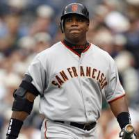 Photo - FILE - In this April 3, 2006, file photo, San Francisco Giants' Barry Bonds grimaces as he walks back to the dugout after flying out during the sixth inning of a baseball game against the San Diego Padres in San Diego. With the cloud of steroids shrouding many candidacies, baseball writers may fail for the only the second time in more than four decades to elect anyone to the Hall. (AP Photo/Denis Poroy, File)