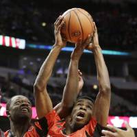 Photo - FILE - In this April 3, 2013, file phto, McDonald's East All-American's Andrew Wiggins (22) and Julius Randle (30) battle for a rebound with McDonald's West All-American's Isaac Hamilton (4) during the second half of the McDonald's All-American Boys basketball game in Chicago. Wiggins signed a letter-of-intent with the University of Kansas at a private ceremony, Tuesday, May 14,  2013, in Huntington, W.Va. The Canadian star averaged 23.4 points and 11.2 rebounds per game this season for West Virginia's Huntington Prep. (AP Photo/Nam Y. Huh, File)