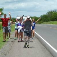 Photo -  People cheer on Mike Wall, of Edmond, as he runs along the Pan-American Highway in Nicaragua during a June visit to the Central American country. Photo provided