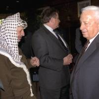 Photo - FILE - In this Oct. 21, 1998 file photo, Israeli Foreign Minister Ariel Sharon, right, stands near but does not look at, or shake hands with, Palestinian leader Yasser Arafat at Wye Plantation, Maryland. Before becoming a candidate, Sharon proudly boasted he had never shaken hands with Arafat, and called the Palestinian leader a