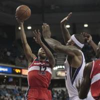 Photo - Washington Wizards guard A.J. Price, left, drives to the basket against Sacramento Kings center DeMarcus Cousins during the first quarter of an NBA basketball game in Sacramento, Calif., Wednesday, Jan. 16, 2013. (AP Photo/Rich Pedroncelli)