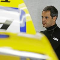 Photo - Driver Juan Pablo Montoya waits as the crew works on his car before practice for the Brickyard 400 Sprint Cup series auto race at the Indianapolis Motor Speedway in Indianapolis, Friday, July 25, 2014. (AP Photo/Darron Cummings)
