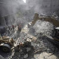 Photo - Palestinians gather around the rubble of a destroyed house following Israeli strikes in the Rafah refugee camp, Southern Gaza Strip, Thursday, Aug. 21, 2014. (AP Photo/Khalil Hamra)