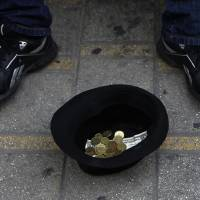 Photo - A hat with money belonging to a musician, is seen on the ground as he plays music at the main shopping street in central capital Nicosia, Cyprus, on Saturday, March 30, 2013. Big depositors at Cyprus' largest bank may be forced to accept losses of up to 60 percent, far more than initially estimated under the European rescue package to save the country from bankruptcy, officials said Saturday. (AP Photo/Petros Karadjias)