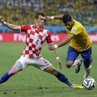Photo - Croatia's Ivan Perisic, left, challenges Brazil's Hulk for the ball during the group A World Cup soccer match between Brazil and Croatia, the opening game of the tournament, in the Itaquerao Stadium in Sao Paulo, Brazil, Thursday, June 12, 2014.  (AP Photo/Felipe Dana)