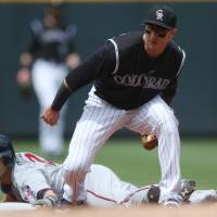 Photo - Colorado Rockies shortstop Troy Tulowitzki, front, fields throw as Minnesota Twins' Brian Dozier slides safely into second base with a double in the first inning of an interleague baseball game in Denver on Saturday, July 12, 2014. (AP Photo/David Zalubowski)