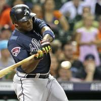 Photo - Atlanta Braves' Justin Upton hits a two-run homer against the Houston Astros in the seventh inning of a baseball game Wednesday, June 25, 2014, in Houston. (AP Photo/Pat Sullivan)