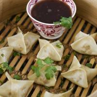 Photo - Vegetarian steamed dumplings with sweet-and-sour sauce.  MATTHEW MEAD - AP