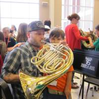Photo - A father tries his hand at playing a French horn under the guidance of his young son during one of the first El Sistema Oklahoma performances held  before Fall Break at Oklahoma City University.  Carla Hinton - The Oklahoman