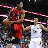 Photo - Toronto Raptors guard DeMar DeRozan (10) drives around New Orleans Pelicans center Greg Stiemsma (34) during the first half of an NBA basketball game in New Orleans, Wednesday, March 19, 2014. (AP Photo/Jonathan Bachman)