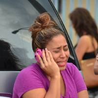 Photo - A woman talks on the phone outside an apartment building at the scene of a fatal shooting in Hialeah, Fla., early Saturday, July 27, 2013. A gunman holding hostages inside the apartment complex killed six people before being shot to death by a SWAT team that stormed the building early Saturday following an hours-long standoff, police said. (AP Photo/El Nuevo Herald, Gaston DeCardenas)
