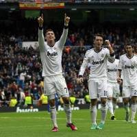 Photo - Real Madrid's Cristiano Ronaldo from Portugal, left, celebrates his goal with Mesut Ozil from Germany, center, during a Spanish La Liga soccer match against Getafe at the Santiago Bernabeu stadium in Madrid, Spain, Sunday, Jan. 27, 2013. (AP Photo/Andres Kudacki)