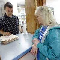 Photo - Brett Whitehead helps Katie Wedemeyer with her medications at the Good Shepherd Ministries' free clinic in Oklahoma City. Photo by Sarah Phipps, The Oklahoman   SARAH PHIPPS - SARAH PHIPPS