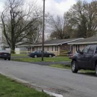 Photo - Police tape is seen around a house in Manchester, Ill., Wednesday, April 24, 2013, where the bodies of five people were found slain early Wednesday in the tiny southwestern Illinois town. Authorities said a suspect was injured and taken into custody. (AP Photo/Regina Garcia Cano)