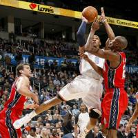 Photo - Oklahoma Cit's Russell Westbrook shoots the ball from between New Jersey's Kris Humphries, left, and Travis Outlaw during the NBA basketball game between the Oklahoma City Thunder and the New Jersey Nets at the Oklahoma City Arena, Wednesday, Dec. 29, 2010.  Photo by Bryan Terry, The Oklahoman