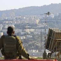 Photo - An Israeli soldier is seen next to an Iron Dome rocket interceptor battery deployed near the northern Israeli city of Haifa, Wednesday, Aug. 28, 2013. Israel ordered a special call-up of reserve troops Wednesday as nervous citizens lined up at gas-mask distribution centers, preparing for possible hostilities with Syria. (AP Photo/Tsafrir Abayov)
