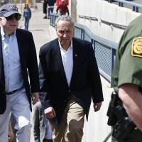 Photo - U.S. Sen. John McCain, R-Ariz., left, and Sen. Chuck Schumer, D-N.Y., tour the Nogales port of entry during their tour of the Mexico border with the United States on Wednesday, March 27, 2013, in Nogales, Ariz. (AP Photo/Ross D. Franklin)