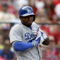 Photo - Los Angeles Dodgers' Yasiel Puig holds his left hand after he was hit by a pitch during the third inning of a baseball game against the St. Louis Cardinals Saturday, July 19, 2014, in St. Louis. Puig left the game in the eighth inning and the Cardinals went on to win 4-2. (AP Photo/Jeff Roberson)