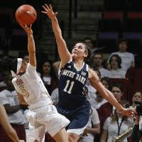 Photo - Florida State guard Cheetah Delgado (5) goes high to score over the defense of Notre forward Dame Natalie Achonwa (11) in the first half of an NCAA college basketball game, Thursday, Feb. 6, 2014, in Tallahassee, Fla. (AP Photo/Phil Sears)