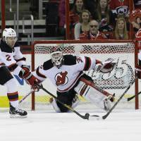 Photo - New Jersey Devils goalie Martin Brodeur (30) and teammate Marek Zidlicky (2), of the Czech Republic, defend the goal against Carolina Hurricanes' Jordan Staal (11) during the first period of an NHL hockey game in Raleigh, N.C., Thursday, March 21, 2013. (AP Photo/Gerry Broome)