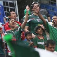 Photo - Mexican supporters shout in the rain before the start of the group A World Cup soccer match between Mexico and Cameroon in the Arena das Dunas in Natal, Brazil, Friday, June 13, 2014.  (AP Photo/Sergei Grits)