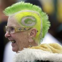 Photo - Green Bay Packers fan Mary Steinkraus of Germantown, Wis., watches the team practice during NFL football training camp Saturday, July 27, 2013, in Green Bay, Wis. (AP Photo/Morry Gash)