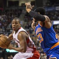 Photo - Toronto Raptors' Kyle Lowry, left, drives at New York Knicks' Toure' Murry during first-half NBA basketball game action in Toronto, Saturday, Dec. 28, 2013. (AP Photo/The Canadian Press, Chris Young)