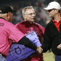Photo - Bethany Superintendent Kent Shellenberger, left, and Washington Superintendent A.J. Brewer, right, shake hands as they present Albert Gray, CEO of The Children's Center, with a check during halftime of their high school football game in Bethany, Okla., on Friday, September 16, 2011. Photo by John Clanton, The Oklahoman