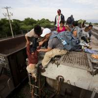 Photo - In this July 12, 2014, photo, a young boy is helped down from a freight car, as Central American migrants board a northbound freight train in Ixtepec, Mexico. Many smugglers take their charges from the southern Chiapas or Oaxaca states to Mexico City on La Bestia, the decrepit freight train, and from there, they choose one of three main routes: to Reynosa in Tamaulipas, Ciudad Juarez in Chihuahua, or cross the Sonoran desert to the outskirts of Mexicali. (AP Photo/Eduardo Verdugo)