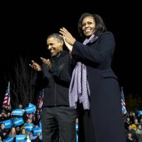Photo -   President Barack Obama and first lady Michelle Obama acknowledge the crowd at his final campaign stop on the evening before the 2012 election, Monday, Nov. 5, 2012, in the downtown Des Moines, Iowa. (AP Photo/Carolyn Kaster)