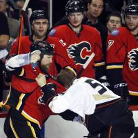 Photo - Anaheim Ducks' Bryan Allen, right, fights with Calgary Flames' Brian Mcgrattan during the first period of an NHL hockey game in Calgary, Alberta, Wednesday, March 12, 2014. (AP Photo/The Canadian Press, Jeff McIntosh)