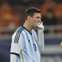 Photo - Argentina's Lionel Messi wipes his mouth after appearing to vomit on the pitch during an international friendly soccer game against Romania on the National Arena stadium in Bucharest, Romania, Wednesday, March 5, 2014. (AP Photo) ROMANIA OUT