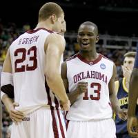Photo - OU / UNIVERSITY OF OKLAHOMA / NCAA TOURNAMENT / CELEBRATION: OU's Blake Griffin, left, and Willie Warren celebrate during a second-round men's NCAA college basketball tournament game between Oklahoma and Michigan in Kansas City, Mo., Saturday, March 21, 2009. Oklahoma won 73-63. PHOTO BY BRYAN TERRY, THE OKLAHOMAN ORG XMIT: KOD