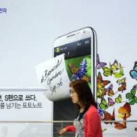 Photo -   Visitors walk by a billboard of Samsung Electronics's product at a showroom of its headquarters in Seoul, South Korea, Friday, Oct. 5, 2012. Samsung Electronics Co. tipped all-time high quarterly operating profit, likely driven by strong sales of high-end smartphones that offset weak semiconductor orders. (AP Photo/Lee Jin-man)