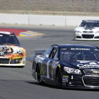 Photo - Jamie McMurray leads Tomy Drissi, left, and Dale Earnhardt Jr., top right, during qualifying for the NASCAR Sprint Cup series auto race Saturday, June 21, 2014, in Sonoma, Calif. McMurray was the pole winner. (AP Photo/Eric Risberg)
