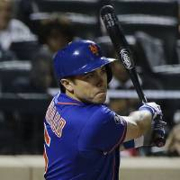 Photo - New York Mets catcher Travis d'Arnaud follows through on a double to center field, allowing Bobby Abreu and Eric Campbell to score, in the eighth inning of a baseball game against the Texas Rangers, Friday, July 4, 2014, in New York. (AP Photo/Julie Jacobson)
