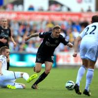 Photo - Swansea City's Gylfi Sigurdsson, left, slides in on Burnley's Matthew Taylor during the English Premier League match at the Liberty Stadium, Swansea, Wales, Saturday Aug. 23, 2014. (AP Photo/PA, Nick Potts)  UNITED KINGDOM OUT  NO SALES  NO ARCHIVE