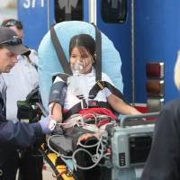 Photo - A student is loaded into an ambulance for treatment of carbon monoxide poisoning after a leak Nov. 11, 2013, at Lee Elementary School in Oklahoma City.