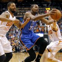 Photo - Oklahoma City Thunder forward Kevin Durant (35) drives between Phoenix Suns guard Goran Dragic, right, of Slovenia, and Markieff Morris during the first half of an NBA basketball game on Sunday, April 6, 2014,in Phoenix. (AP Photo/Matt York)
