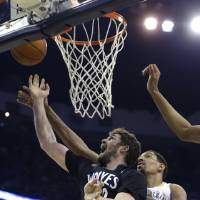 Photo - Minnesota Timberwolves power forward Kevin Love goes to the basket in front of New Orleans Pelicans center Alexis Ajinca (42) in the first half of an NBA basketball game in New Orleans, Friday, Feb. 7, 2014. (AP Photo/Gerald Herbert)