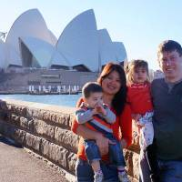 Photo - In this undated photo provided by the Rhodes family, Phoumalaysy Rhodes, second left, and her husband Gavin Rhodes, right, hold their children Manfred and Jadesuda, second right, near the Sydney Opera House in Sydney, Australia. The four are among 49 passengers and crew believed killed when a Lao Airlines plane crashed on Wednesday, Oct. 16, 2013, en route from the Lao capital Vientiane to Pakse in the Southeast Asian nation's south. (AP Photo/Rhodes Family)