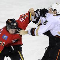 Photo - Anaheim Ducks' Ben Lovejoy, right, briefly fights with Calgary Flames' Mikael Backlund, from Sweden, during first period NHL action in Calgary, Alberta, Friday, April 19, 2013.  (AP Photo/The Canadian Press, Larry MacDougal)