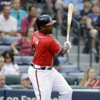 Photo - Atlanta Braves' Justin Upton hits a single to score teammate Jason Heyward, not pictured, in the first inning of a baseball game against the Arizona Diamondbacks, Friday, June 28, 2013, in Atlanta. (AP Photo/David Goldman)