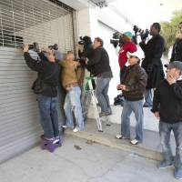 Photo - Photographers jockey for position as they wait for police to transport pop singer Justin Bieber, Thursday, Jan. 23, 2014 in Miami Beach, Fla. Police have Bieber and R&B singer known as Khalil for alleged drag-racing on a Miami Beach street. (AP Photo/Wilfredo Lee)