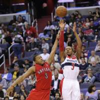 Photo - Washington Wizards guard Bradley Beal, right, takes a shot against Toronto Raptors guard Kyle Lowry, left, during the second half of an NBA basketball game, Sunday, March 31, 2013, in Washington. The Wizards won 109-92. (AP Photo/Nick Wass)
