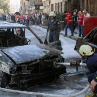 Photo - Firefighters extinguish a burning vehicle after two mortar rounds struck the Abu Roumaneh area in Damascus, Syria, Saturday, Oct. 12, 2013. Syria's state news agency said two mortar rounds struck an upscale neighborhood in the Syrian capital of Damascus, killing at least one child and injuring a dozen people. (AP Photo)