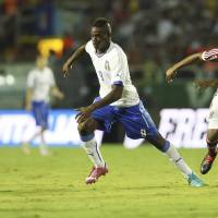 Photo - Italy's national soccer team player Mario Balotelli, left, dribbles past Fluminense's Valencia during a World Cup warm up soccer match between Italy and Fluminense at the Cidadania stadium, in Volta Redonda, Brazil, Sunday, June 8, 2014. Italy plays in group D of the 2014 soccer World Cup. (AP Photo/Antonio Calanni)