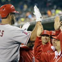 Photo - Los Angeles Angels' Albert Pujols (5) is congratulated in the dugout after hitting a three-run home run during the sixth inning of a baseball game against the Detroit Tigers in Detroit, Friday, April 18, 2014. (AP Photo/Carlos Osorio)